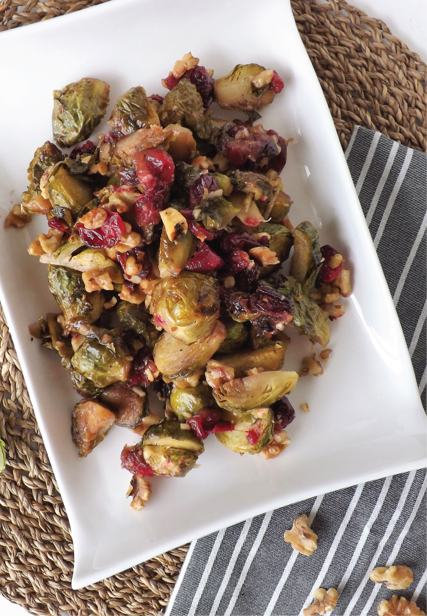 Plate of finished dish - Maple Dijon Roasted brussel sprouts with walnuts and cranberries.